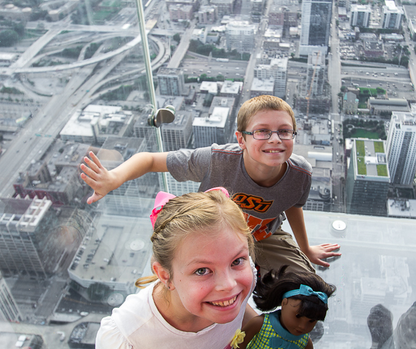 Sit on the ledge of Skydeck in Chicago with kids.